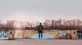 Adolescente que se coloca al borde de un embarcadero cerca del agua Foto de archivo