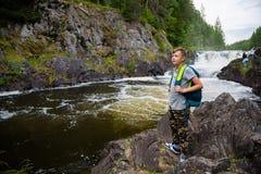 Adolescente que se coloca cerca de la cascada Imagenes de archivo