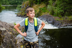 Adolescente que se coloca cerca de la cascada de la montaña Imagenes de archivo