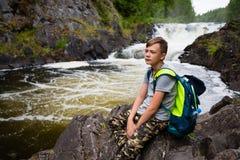 Adolescente que se coloca cerca de la cascada de la montaña Fotos de archivo