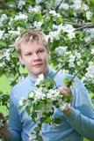Adolescente que se coloca cerca de manzano floreciente. Foto de archivo