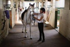 Adolescente que se coloca con el caballo Fotografía de archivo