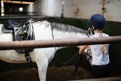 Adolescente que se coloca con el caballo Fotos de archivo libres de regalías