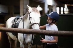 Adolescente que se coloca con el caballo Foto de archivo libre de regalías