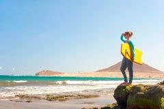Adolescente que se coloca con la tabla hawaiana en coas de la roca de Océano Atlántico Imagen de archivo