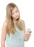 Adolescente que se coloca con un teléfono en su mano Imagen de archivo libre de regalías