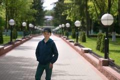 Adolescente que se coloca en el callejón en parque del verano Imagenes de archivo