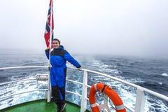 Adolescente que se coloca en el velero en traje de la protección en día de niebla Foto de archivo libre de regalías