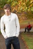 Adolescente que se coloca en parque del otoño con la hembra Imagen de archivo libre de regalías