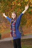 Adolescente que se coloca en parque del otoño con los brazos hacia fuera Imagenes de archivo