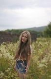 Adolescente que se coloca en un campo de flores Fotografía de archivo