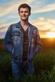 Adolescente que se coloca en un campo de trigo en la puesta del sol Foto de archivo