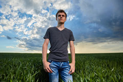 Adolescente que se coloca en un campo de trigo en la puesta del sol Foto de archivo libre de regalías