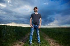 Adolescente que se coloca en un campo de trigo en la puesta del sol Imágenes de archivo libres de regalías