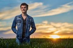 Adolescente que se coloca en un campo de trigo en la puesta del sol Fotos de archivo