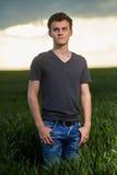 Adolescente que se coloca en un campo de trigo en la puesta del sol Imagen de archivo libre de regalías