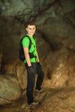 Adolescente que se coloca en una cueva Imagen de archivo