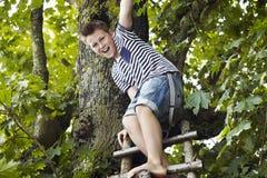 Adolescente que se coloca en una escalera de madera, sonriendo Fotografía de archivo