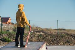 Adolescente que se coloca en una sudadera con capucha amarilla que sostiene un monopatín de la mano en los tugurios urbanos del f Foto de archivo libre de regalías