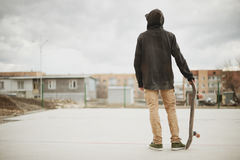 Adolescente que se coloca en una sudadera con capucha negra que sostiene un monopatín de la mano en los tugurios urbanos del fond Foto de archivo