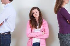 Adolescente que se coloca entre los padres que no hablan el uno al otro Fotos de archivo libres de regalías