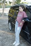 Adolescente que se coloca que se inclina en su coche Fotografía de archivo