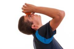 Adolescente que se considera anaranjado en su frente Imagenes de archivo