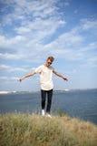Adolescente que se divierte cerca del río Un individuo joven elegante en un fondo natural Concepto casual de la moda Copie el esp Foto de archivo libre de regalías