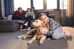 Adolescente que se divierte con el perro del golden retriever mientras que amigos que se sientan en el sofá Foto de archivo