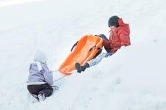 Adolescente que se divierte el invierno mientras que juega con su hermana del hermano al aire libre en la colina de la nieve Fotografía de archivo