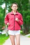 Adolescente que se ejecuta en parque verde Imagen de archivo libre de regalías