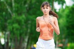 Adolescente que se ejecuta en parque verde Imágenes de archivo libres de regalías