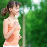 Adolescente que se ejecuta en parque verde Foto de archivo libre de regalías
