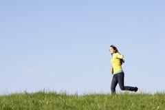 Adolescente que se ejecuta a través de prado del verano Foto de archivo libre de regalías
