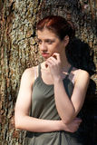 Adolescente que se inclina al árbol Foto de archivo