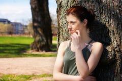 Adolescente que se inclina al árbol Imagen de archivo libre de regalías