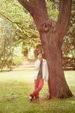 Adolescente que se inclina contra un árbol Imagenes de archivo