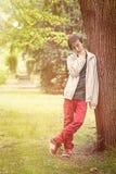 Adolescente que se inclina contra un árbol Foto de archivo libre de regalías