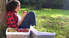 Adolescente que se inclina contra un árbol en una huerta que come una manzana usando su teléfono elegante de la célula móvil almacen de video