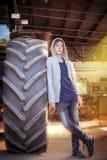 Adolescente que se inclina contra un neumático enorme Fotografía de archivo