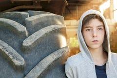 Adolescente que se inclina contra un neumático enorme Imagenes de archivo