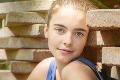 Adolescente que se inclina contra una pila de losas Imagen de archivo