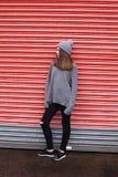 Adolescente que se inclina contra una puerta shuttered Imágenes de archivo libres de regalías