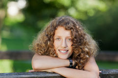 Adolescente que se inclina en banco en el parque Imagenes de archivo
