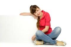 Adolescente que se inclina en el cartel en blanco Foto de archivo