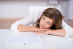 Adolescente que se inclina en el escritorio mientras que mira lejos Foto de archivo