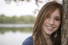 Adolescente que se inclina en un árbol cerca de un lago Imagen de archivo libre de regalías