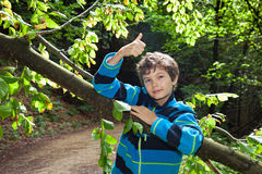 Adolescente que se inclina en un tronco, pulgares-Para arriba. Fotografía de archivo
