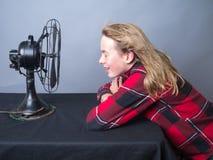 Adolescente que se refresca apagado delante de ventilador Imagen de archivo
