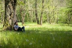 Adolescente que se relaja bajo un árbol Imagenes de archivo